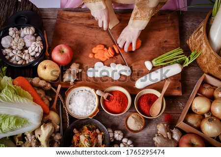Girl wearing hanbok, making chopped kimchi, radish and carrots to mix with Chinese cabbage. Korean food concept from folk wisdom Royalty-Free Stock Photo #1765295474