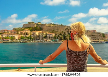 Caucasian blonde woman with a surgical mask during Covid-19 on ferry boat to Elba Island looking Portoferraio city. Italian tourist woman travels on Elba. Coronavirus holiday travel in Europe. Royalty-Free Stock Photo #1765299503