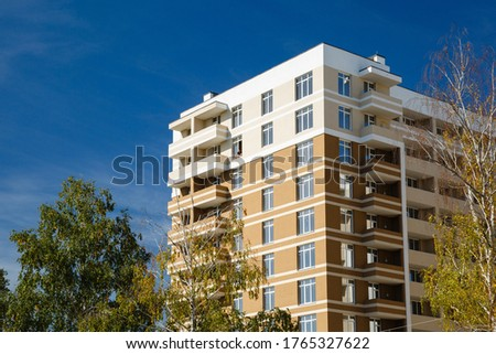 New-constructed unfinished multi-storey residential building. multi-storey residential house in brown and beige colors. Modern residential construction. Residential fund. Building on background of sky #1765327622