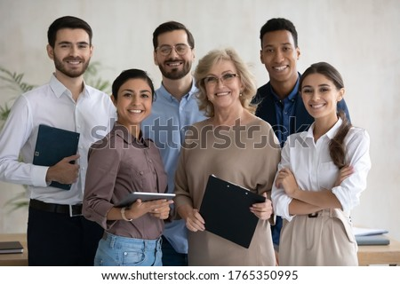 Corporate portrait smiling diverse employees team standing in office, looking at camera, successful happy workers with middle aged leader posing for photo, motivated staff, workforce Royalty-Free Stock Photo #1765350995