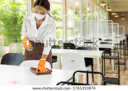 Portrait attractive asian waitress wear face mask and face shield cleaning table with alcohol and wet wipe before welcome customer. New normal hygiene restaurant concept. #1765393874