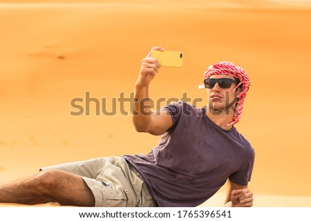 Handsome young male traveler taking a selfie picture with his mobile phone while laying on a golden sand dune of the Arabian desert. Travel and tourism.