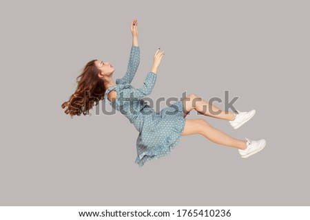 Hovering in air. Relaxed beautiful girl ruffle dress and curly soaring hair levitating, flying in dream with hands up, reaching for something high. indoor studio shot isolated on gray background Royalty-Free Stock Photo #1765410236