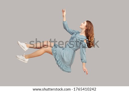Hovering in air. Cheerful smiling pretty girl in vintage ruffle dress levitating flying in mid-air, looking up happy dreamy and raising hand to catch. indoor studio shot isolated on gray background #1765410242