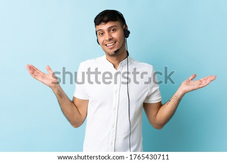 Telemarketer Colombian man working with a headset over isolated background with shocked facial expression