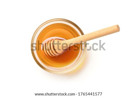 Flat lay (top view) of Glass bowl of pure honey with honey dipper isolated on white background. Clipping path. Royalty-Free Stock Photo #1765441577