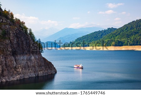 Pictures of the Fagaras Mountain. Carpathians. Romania. A beautiful landscape with the Vidra lake. A ship on the lake. The calm water of the storage lake Vidra.