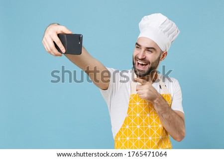 Funny young bearded male chef or cook baker man in apron white t-shirt toque chefs hat isolated on blue wall background. Cooking food concept. Doing selfie shot pointing index finger on mobile phone