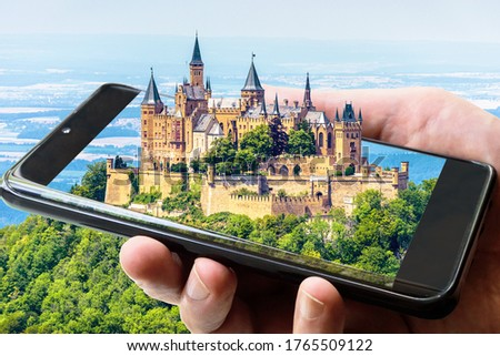 Hohenzollern Castle atop mount, Germany. Picture of fairytale Gothic castle on smartphone, amazing photograph of landscape and mobile or cell phone. Concept of travel, summer adventure and technology.