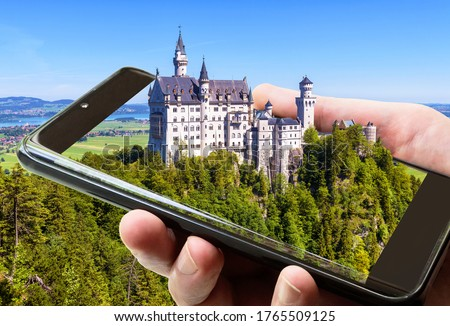 Neuschwanstein castle in Bavaria, Germany. Taking picture of fairytale castle by mobile or cell phone, photo of landscape and Neuschwanstein on smartphone screen. Concept of travel and technology.