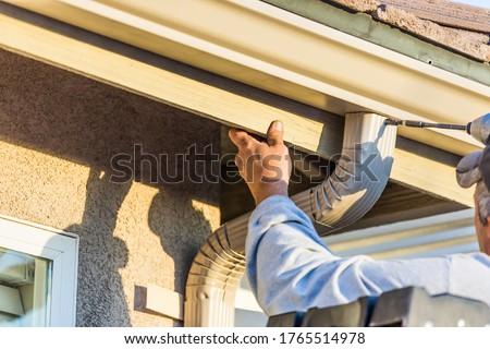 Worker Attaching Aluminum Rain Gutter and Down Spout  #1765514978