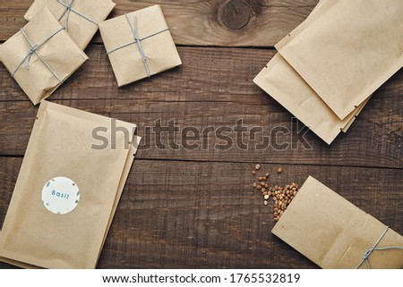 Paper bags with seeds for planting. Wooden table. View from above. Royalty-Free Stock Photo #1765532819