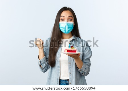 Social distancing lifestyle, covid-19 pandemic, celebrating holidays during coronavirus concept. Rejoicing happy asian girl in medical mask celebrating birtday, triumphing as hold bday cake