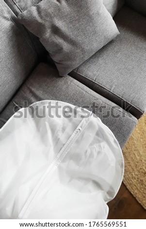Wedding Dress in White Hanging Garment Bag on the Couch. The morning before the wedding. Royalty-Free Stock Photo #1765569551