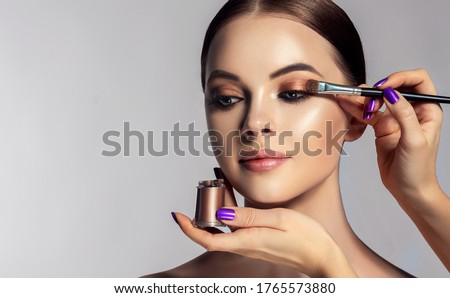 Makeup artist applies  eye shadow  . Beautiful woman face. Hand of visagiste, painting  cosmetics of young beauty  model girl . Make up in process Royalty-Free Stock Photo #1765573880