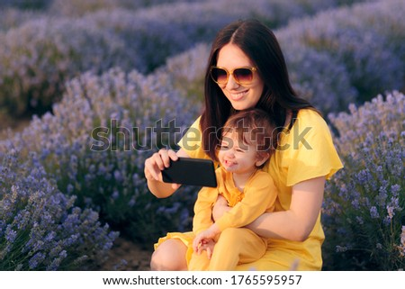 Mother and Baby Taking Selfies in Lavender Field. Candid moment with mom and daughter taking travel pictures