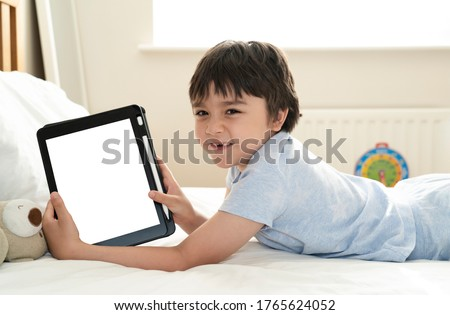 Kid 6-7 year old boy watching cartoon on tablet, Asian child lying in bed showing digital tunch pad, Happy Kid having fun and relaxing on his own in bed room,New normal lifestyle