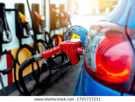 Car fueling at gas station. Refuel fill up with petrol gasoline. Petrol pump filling fuel nozzle in fuel tank of car at gas station. Petrol industry and service. Petrol price and oil crisis concept. #1765717211