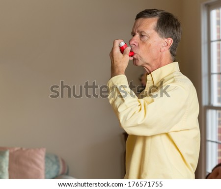 Senior caucasian man at home with asthma inhaler to handle problems with breathing #176571755