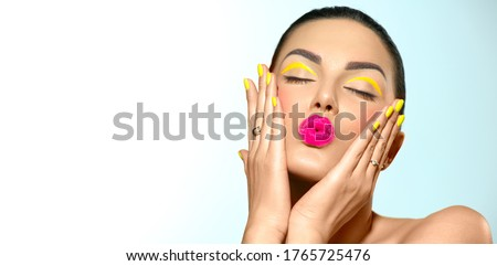 Beauty model girl with fashion make-up, Bright yellow eye line and nails, trendy manicure. Eye make-up creative ideas. Summer makeup. Kiss gesture. Beautiful young woman portrait. Face closeup Royalty-Free Stock Photo #1765725476