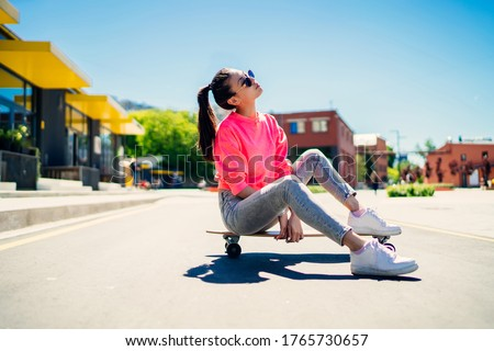 Attractive female teenager in stylish sunglasses resting at longboard during sport hobby in city, young Asian woman dressed in trendy girlish streetwear enjoying recreation chill at skateboard Royalty-Free Stock Photo #1765730657