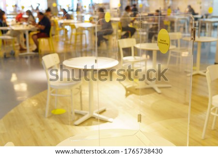 Cleary acrylic / plastic divider or barrier on table in food court as part of safety protection for customers. New normal & Social distancing during Covid-19 pandemic  #1765738430