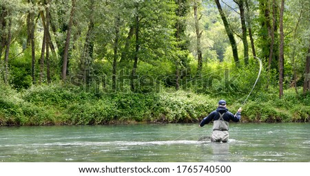 fly fisherman with black jacket fishing in the middle of the river in a mountain river in summer Royalty-Free Stock Photo #1765740500