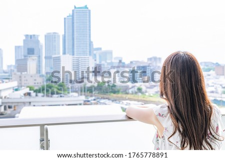 Young woman admiring the city scenery on the balcony Royalty-Free Stock Photo #1765778891