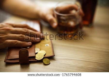 Fired man countsing his last money to drink expensive alcohol. Wrinkled alcoholic sits at brown wooden table with a glass of cognac with ice, on the table, empty wallet with coins Royalty-Free Stock Photo #1765794608