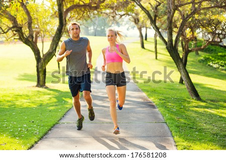 Athletic couple running together. Sport runners jogging on park trail in the early morning.  Healthy lifestyle fitness concept #176581208