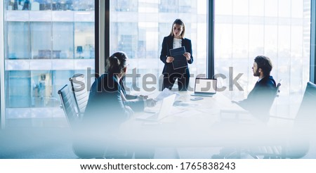 High angle of serious female executive manager in classy suit standing in front of group of colleagues and explaining business strategy during meeting in modern workplace #1765838243
