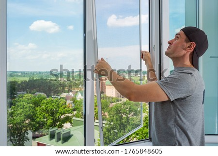 A contractor worker installing mosquito wire screen on house plastic windows to protect from insects. Royalty-Free Stock Photo #1765848605