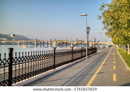 Morning landscape with view to sidewalk along Danube river with view to Margaret Bridge in Budapest, Hungary on a background of clear blue sky. #1765855829