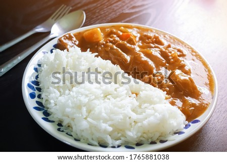 Selective focus of Japanese beef curry serve on plate with rice, picture with warm window light