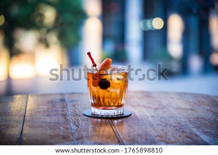 you can see a rum old fashioned on ice cocktail on a wooden table the color of which is orange transparent with a blurred background Royalty-Free Stock Photo #1765898810