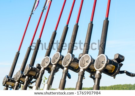 Fishing trolling boat rods in rod holder. Big game fishing. Fishing reels and rods pattern on boat. Sea fishing rods and reels in a row #1765907984