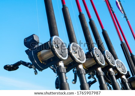Fishing trolling boat rods in rod holder. Big game fishing. Fishing reels and rods pattern on boat. Sea fishing rods and reels in a row #1765907987