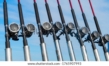 Fishing trolling boat rods in rod holder. Big game fishing. Fishing reels and rods pattern on boat. Sea fishing rods and reels in a row #1765907993