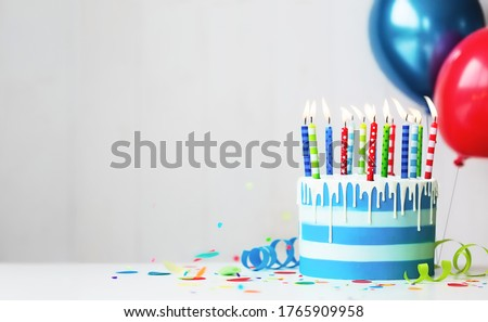 Colorful striped buttercream birthday cake with birthday candles and balloons Royalty-Free Stock Photo #1765909958