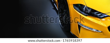 Front headlights of yellow modern car on black background,copy space #1765918397