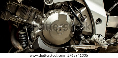 Silver engine of sports motorcycle closeup. Gearbox, front wheel motorbike.  Chrome engine parts, pistons, cylinder, pedals. Color style. Repair bike maintenance in garage. Banner for web site