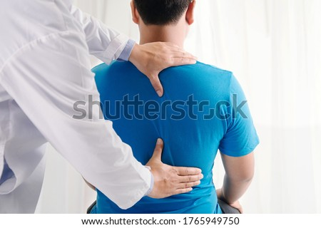 Doctor physiotherapist doing healing treatment on man's back.Back pain patient, treatment, medical doctor, massage therapist.office syndrome Royalty-Free Stock Photo #1765949750