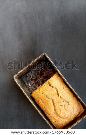 Fresh baked homemade pumpkin bread with part cut away in vintage pan over dark background. Image shot from top view, flatlay.