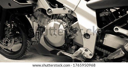 Side of motorcycle close-up. Chain, gearbox, front wheel motor bike. Sepia monochrome. Chrome engine parts, pistons, cylinder. Vintage style. Repair, maintenance in garage. Banner for web site