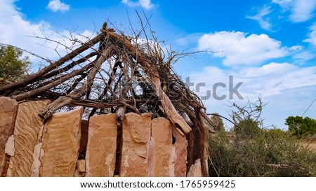 Broken Rajasthani hut with clouds and blue sky #1765959425