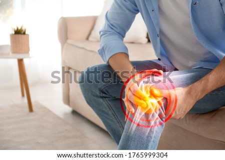 Man suffering from knee pain at home, closeup Royalty-Free Stock Photo #1765999304