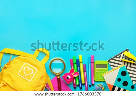 Frame from school and office supplies Paper clips, scissors, pens, felt-tip pens, sharpener, calculator, stapler isolated on blue background Flat lay Top view Back to school, education concept Mock up