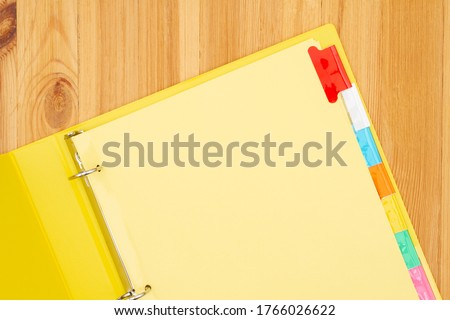 Blank file tabs in a yellow binder on wood desk mockup with copy space for your school or business message Royalty-Free Stock Photo #1766026622
