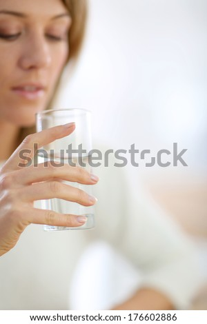 Closeup on glass of water held by woman's hand #176602886