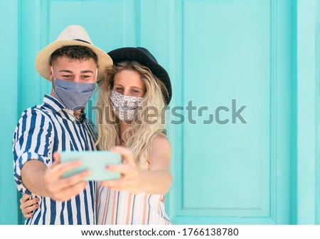 Young couple wearing face mask taking selfie with mobile smartphone on vacation - People having fun traveling again during corona virus outbreak - Love relationship and technology concept  #1766138780